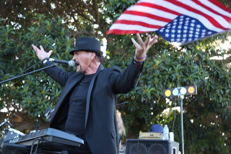 Bill singing in front of American flag